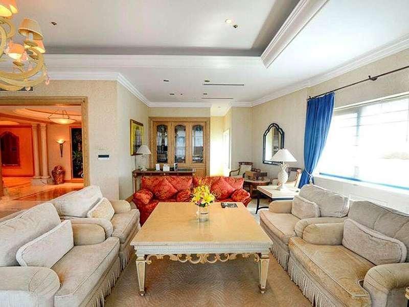 Phòng khách được phủ một màu xanh ngọc lục bảo nhưng không đơn điệu khi có những chiếc ghế màu hồng nhỏ nhắn